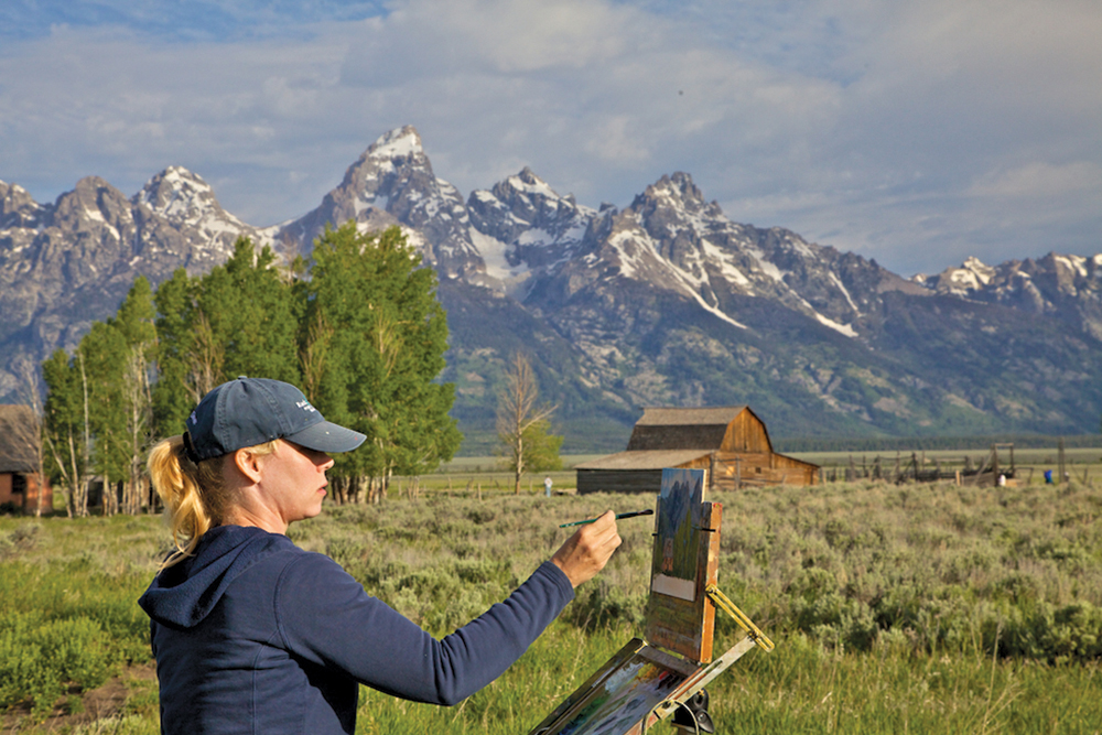 Artist Kim Casebeer painting outdoors with the Teton mountains in the background