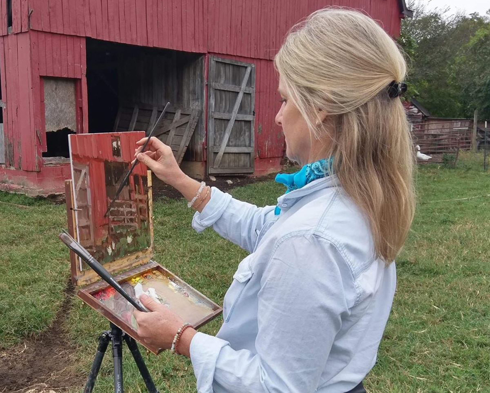 Female artist painting a barn on location